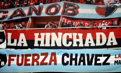 A banner reading 'Be strong Chávez' is displayed at a Venezuelan football match