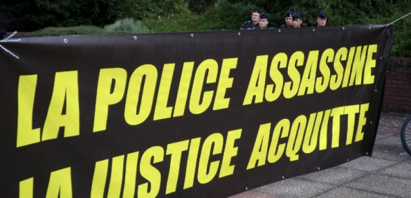 Policemen stand behind a banner reading