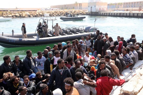 Libyan coast guards watch over illegal migrants, who had hoped to set off to Europe with the help of people smugglers from the coastal town of Garabulli, after their vessel was escorted by the Libyan navy to the capital, Tripoli, prior to their arrest on June 6, 2015. Libya has a coastline of 1,770 kilometres (more than 1,000 miles). It is just 300 kilometres from the Italian island of Lampedusa, which many migrants fleeing poverty and conflict aim for as their gateway to Europe. AFP PHOTO / MAHMUD TURKIA